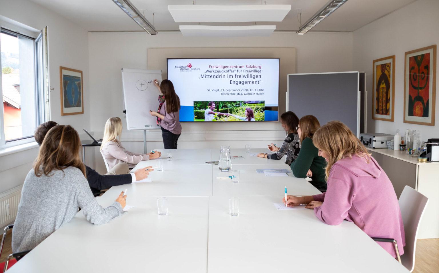 Personen sitzen bei einem Workshop, besprechen Tätigkeiten des Freiwilligenzentrum Salzburg