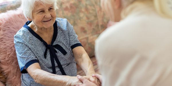 Female home carer supporting old woman to stand up from the sofa at care home